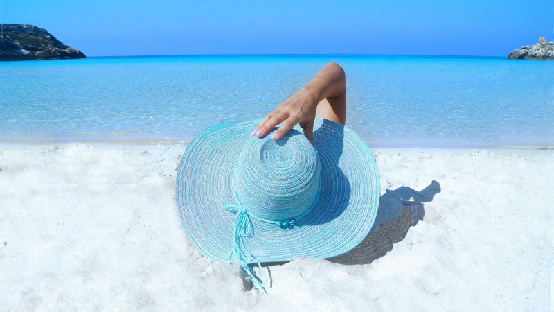 Lady On Beach In Hat Wearing Reef Safe Waterproof Sunscreen For The Beach Boat Scuba Diving