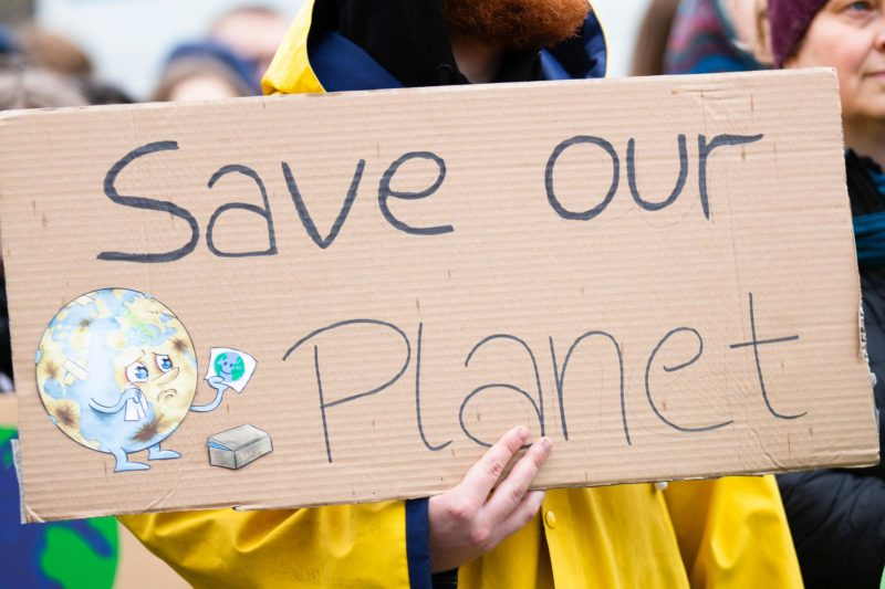 man holding Save Our Planet placard